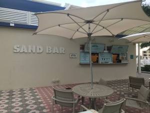 Sabd Bar Grill Walk-up window with menus and tables and chairs under umbrellas for seating